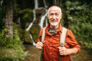 Portrait of a Senior hiker standing next to the mountain creek