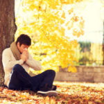 healthcare and medicine concept - ill man with paper tissue in autumn park